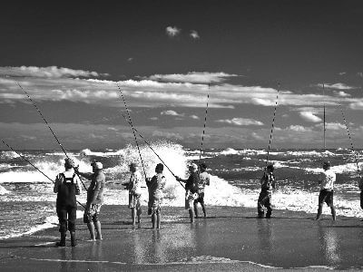 A group of people surf fishing
