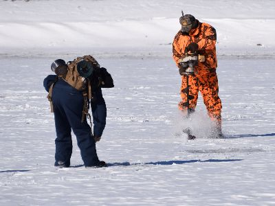 Drilling a hole to go ice fishing