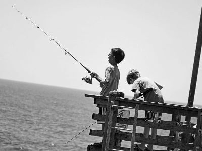Two boys fishing off a pier